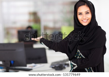 attractive young Arabian businesswoman presenting office - stock photo