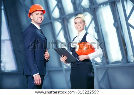 Attractive young architect and his colleague are discussing plan of building a construction. They are standing and smiling. The woman is holding a folder of documents and an orange helmet - stock photo