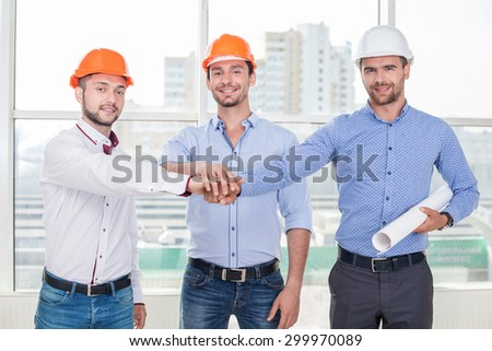 Attractive young architect and two builders are joining their hands together. They are smiling friendly. The men trust to each other. They are the real team
