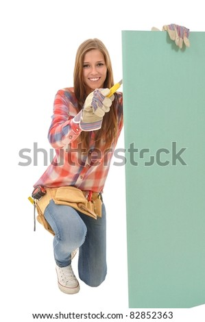 Attractive young artisan edited with yellow knife a plasterboard - stock photo
