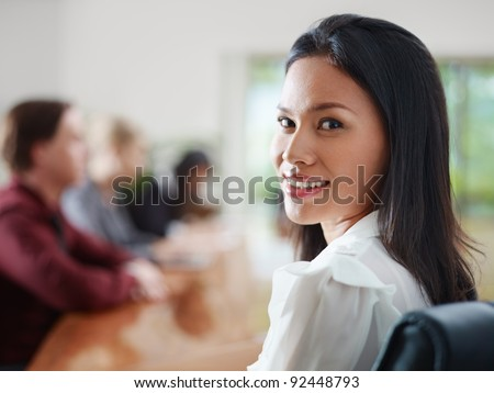 Attractive young Asian business woman smiling and looking over shoulders at business meeting with co-workers. - stock photo