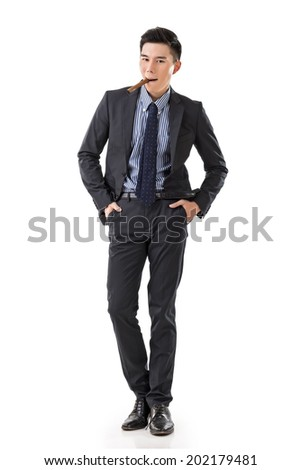 Attractive young Asian businessman holding a cigar, full length portrait isolated on white background.