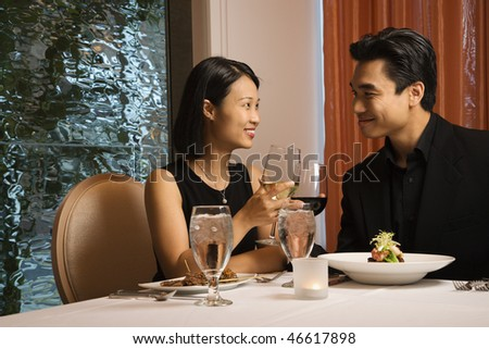 Attractive young Asian couple sit at a restaurant table smiling and toasting. Horizontal shot.