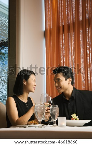 Attractive young Asian couple sit at a restaurant table smiling and toasting their wine. Vertical shot. - stock photo