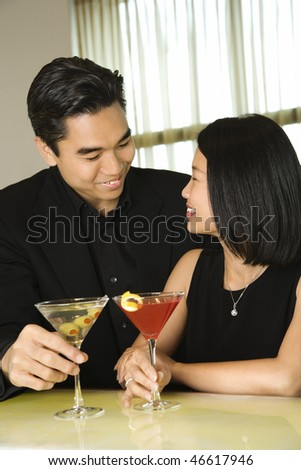 Attractive young Asian couple smiling and facing each other while holding cocktails at a bar. Vertical shot.