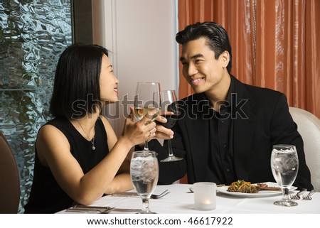 Attractive young Asian couple toast their wine at a restaurant table. Horizontal shot. - stock photo