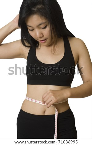 Attractive young Asian girl with measuring tape around her waist - stock photo