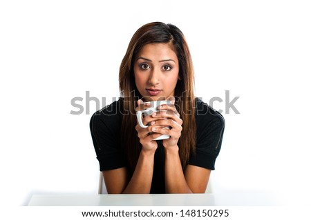Attractive young asian indian woman enjoying a nice warm drink  - stock photo