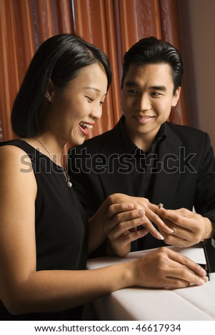 Attractive young Asian man places an engagement ring on an attractive young Asian woman. Vertical shot.