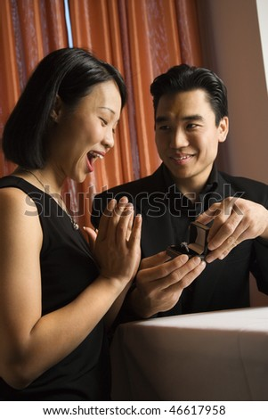 Attractive young Asian man proposes to an attractive Asian woman with an engagement ring. Vertical shot.