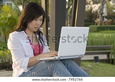 attractive young Asian woman is outdoors with laptop computer