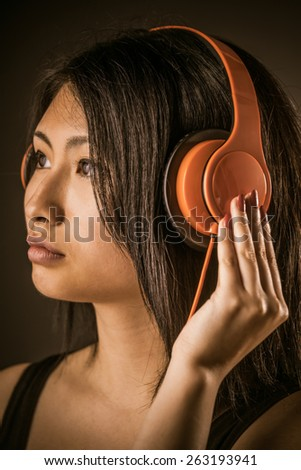 Attractive young Asian woman listening to her music on stereo headphones looking ahead with a dreamy expression and her hand to her ear