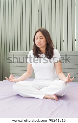 Attractive young asian woman practicing yoga meditation at sunrise - stock photo