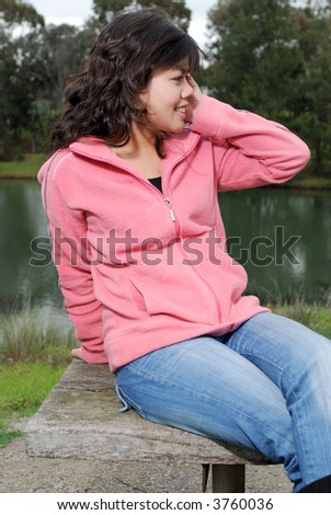 Attractive young asian woman talking on the phone - stock photo