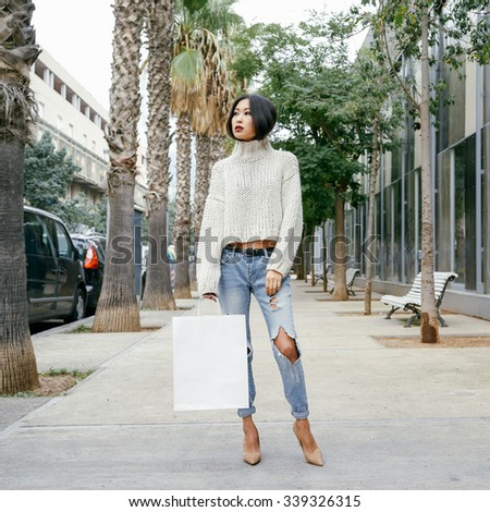 Attractive young Asian woman with paper bags walking on city street. Copy space on shopping bags.