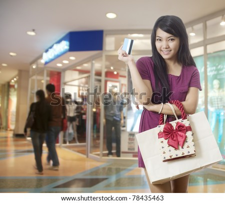 Attractive young Asian woman with shopping bags at the mall - stock photo