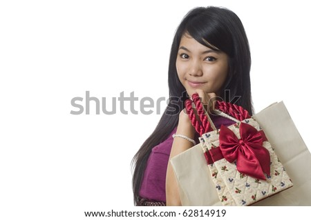 Attractive young Asian woman with shopping bags isolated on white - stock photo