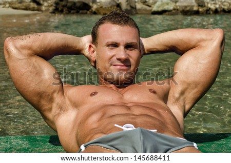 Attractive young, athletic muscle man on the beach with arms behind his head - stock photo
