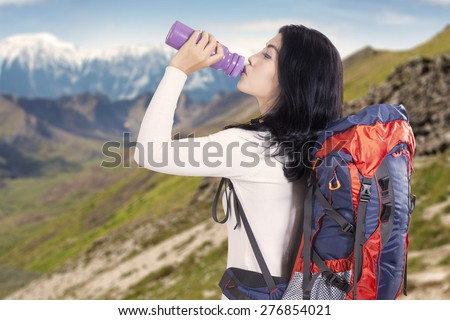 Attractive young backpacker drinking fresh water while carrying backpack for hiking on the mountainside - stock photo