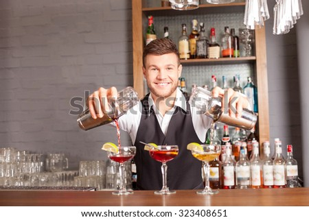 Attractive young bartender is preparing cocktails in pub. He is standing and holding two shakers. The man is pouring mixed drink into glasses. He is looking at camera and smiling - stock photo