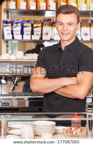 attractive young bartender making coffee. handsome male smiling behind counter