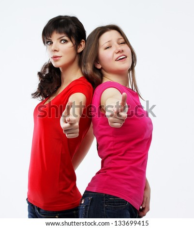 Attractive young beautiful female friends pointing at camera - stock photo