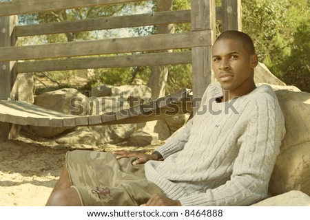 attractive young black man sitting in a park - stock photo