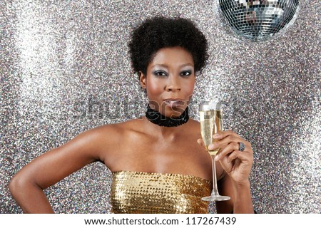 Attractive young black woman holding a champagne glass while standing in a night club with a mirror ball and a silver glitter background. - stock photo