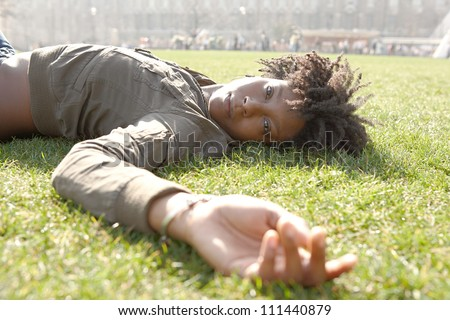 Attractive young black woman laying down on green grass in the city of London on a sunny day, looking at camera and relaxing.