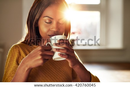 Attractive young black woman sitting at a table at home backliot by a bright sun enjoying a cup of fresh coffee with her eyes closed in bliss - stock photo