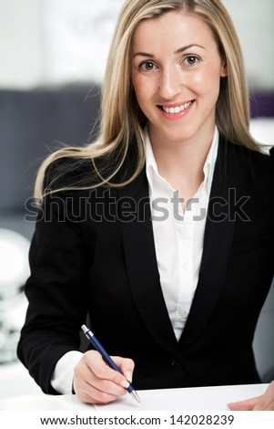 Attractive young blond businesswoman sitting at her desk with a pen in her hand looking at the camera
