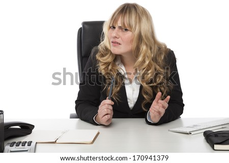 Attractive young blond businesswoman with a quizzical expression peering sideways at the camera in confusion as she struggles to understand something - stock photo