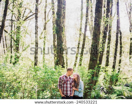 Attractive Young Blond Couple in forest looking at each other - stock photo