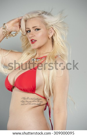 Attractive young blond girl wearing a two piece red swimsuit in a studio with blue eyes.
