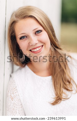 Attractive Young Blond leaning against white wall, looking at camera, smiling