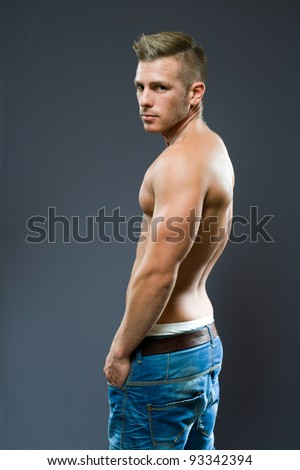 Attractive young blond man looking back over his shoulder.