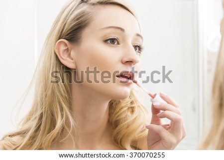 Attractive young blond woman applying lip gloss to her lips to enhance the color and shine in the bathroom mirror in a beauty and glamour concept