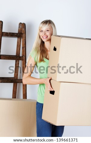 Attractive young blond woman carrying brown cardboard packing cartons as she moves house to new premises - stock photo