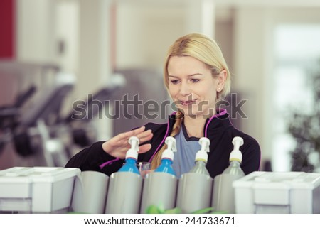 Attractive young blond woman dispensing isotonic high energy juice in a gym from a vending machine - stock photo