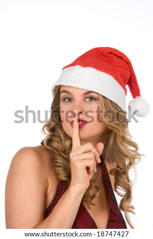 Attractive young blond woman in Christmas hat with finger on her lips - stock photo