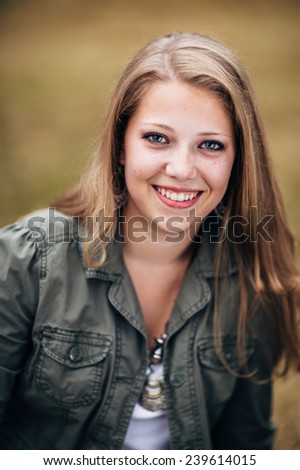 Attractive Young Blond Woman in green jacket close up - stock photo
