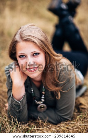 Attractive Young Blond Woman laying in straw feet up, slight smile close up - stock photo