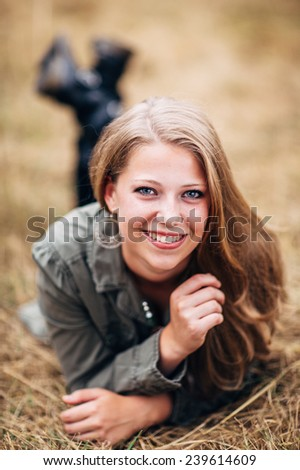 Attractive Young Blond Woman laying in straw feet up smiling - stock photo