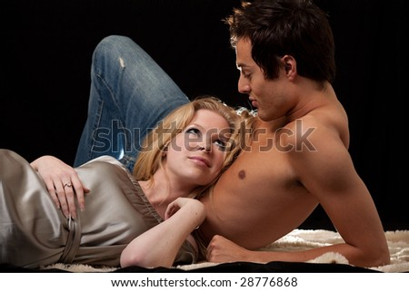 Attractive young blond woman laying on the bare chest of attractive young brunette man - stock photo