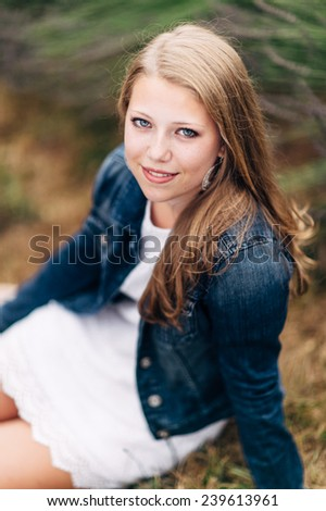 Attractive Young Blond Woman sitting on ground, smiling, jean jacket - stock photo