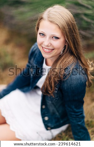 Attractive Young Blond Woman sitting on ground, smiling, jean jacket variation - stock photo