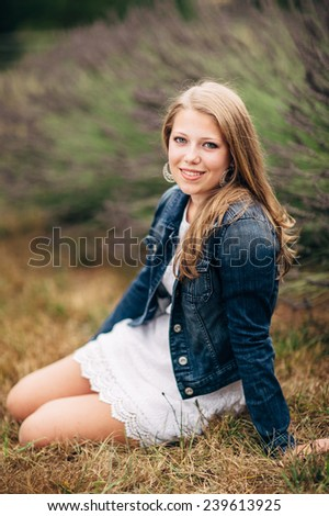 Attractive Young Blond Woman sitting on ground, smiling, jean jacket vertical