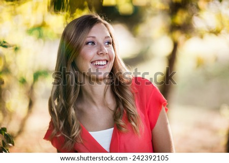 Attractive Young Blond Woman Smiling Under a tree looking away from camera - stock photo