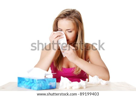 Attractive young blond woman using a tissue. - stock photo