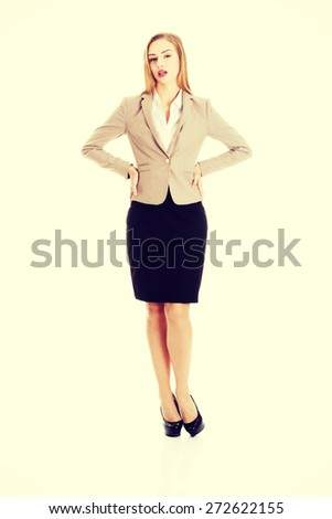 Attractive young blonde businesswoman standing - stock photo